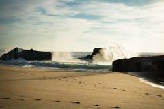 Enormes Wellenwasserspritzen hinter Blockhaus auf szenischem schönem Meerblick des sandigen Strandes mit dem Spritzen bewegt well Stockfotografie