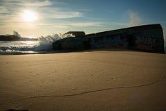 Enormes Wellenwasserspritzen hinter Blockhaus auf szenischem schönem Meerblick des sandigen Strandes mit dem Spritzen bewegt well Lizenzfreies Stockbild