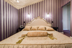 Enormous bed inside baroque bedroom Stock Images