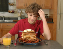 The enormous breakfast. Boy ponders what to do with a huge pile of pancakes, sausage, and bacon Stock Photo