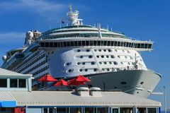 Massive Cruise Liner With Dockside Restaurant in Foreground. An enormous cruise liner dwarfs the roof and red shade umbrellas of a restaurant. This image was royalty free stock photos