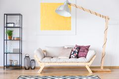 Enormous lamp standing by couch. Enormous lamp entangled with a black cable standing by a cozy couch with many pillows royalty free stock photo