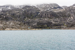 Enormous rocks, small house, Greenland Stock Photos
