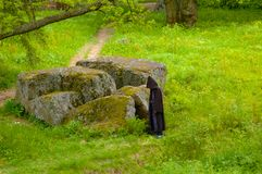Enormous stone in a park. Figure in a black cloak next to enormous stone in a park Royalty Free Stock Image