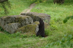 Enormous stone in a park. Figure in a black cloak next to enormous stone in a park Royalty Free Stock Photo