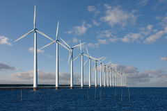 Enormous windmills standing in the sea. Along a Dutch seabarrier royalty free stock images