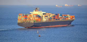 Enormt behållarelastfartyg som är utgående från port Royaltyfria Foton