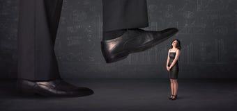 Enormt ben som kliver på ett mycket litet businnesswomanbegrepp Royaltyfri Fotografi