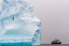 Enormt stycke av isberget med antarctickryssningskeppet på horisonten, arkivfoton