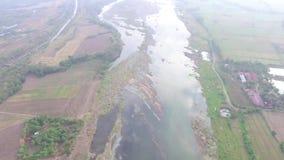 Enormt tyst skumt grunt flodvatten som flödar i liten by för bruka gemenskap låg flygasurrantenn stock video