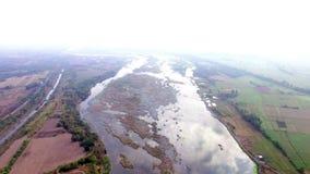 Enormt tyst skumt grunt flodvatten som flödar i liten by för bruka gemenskap låg flygasurrantenn arkivfilmer