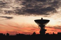 Enormt vitt radioteleskop av en satellit- maträtt mot himlen under solnedgång Arkivfoton