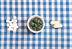 Enough Pills To Go Around. Three groups of pills on a blue and white checkered table cloth royalty free stock image