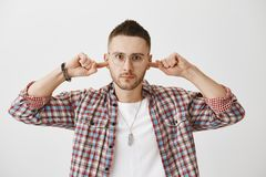 Enough of your excuses, I am done with you. Portrait of angry or annoyed young man with beard, wearing trendy glasses. And plaid shirt, covering ears with index Stock Images