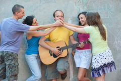 Enough with your singing. Four young people preventing fifth amoung them from singing while playing acoustic guitar stock images