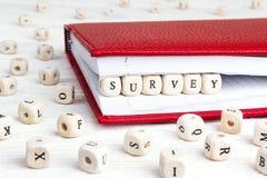 Enquête de Word écrite dans les blocs en bois dans le carnet rouge sur la table en bois blanche photographie stock libre de droits