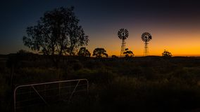 Enquanto o sol aumenta, os moinhos de vento da exploração agrícola estão mostrados em silhueta contra a luz dourada fotos de stock royalty free