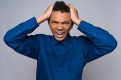 Enraged African American teenager grabs for head. Royalty Free Stock Photography