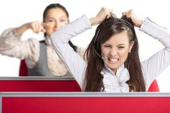 Enraged call center agent. Angry frustrated call center female agent screaming and pulling her hair in rage with female colleague pointing at her from behind Royalty Free Stock Photography