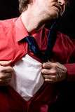 Enraged man rips off a red shirt on a black background Stock Photography