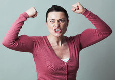 Enraged 40s woman flexing her muscles up for metaphor. Muscle concept - enraged 40s woman flexing her muscles up for metaphor of female independence and power Stock Images