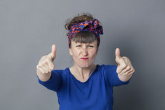 Enraged woman frowning with thumbs up for fighting success. Optimism concept - enraged 30s woman frowning with two thumbs up in the foreground for fighting Royalty Free Stock Photos