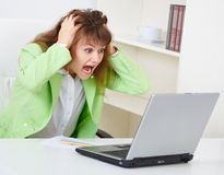 Enraged woman reads news in Internet Stock Photo