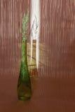 Enrarezca la botella verde con las puntillas del espárrago dentro y afuera Glar Imagen de archivo libre de regalías