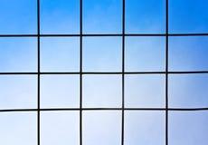 Enrede el acero negro en fondo brillante del cielo azul imagen de archivo