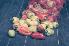 Enrede el bolso con pimientas dulces coloridas en el piso de madera viejo SE fotografía de archivo
