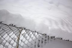 Enrede la cerca bajo capa gruesa de nieve después de nevadas fotografía de archivo
