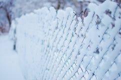 Enrede la cerca cubierta en una capa gruesa de nieve foto de archivo
