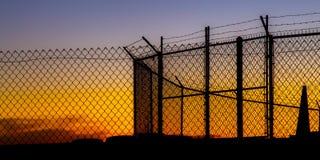 Enrede la cerca de alambre y el alambre del barbeb en la puesta del sol imágenes de archivo libres de regalías