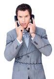 Enredo enojado del hombre de negocios para arriba en alambres del teléfono Foto de archivo libre de regalías