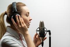 Enregistrement vocal femelle Jeune fille avec le microphone et les écouteurs dans le studio d'enregistrement Enregistrement de vo photos libres de droits