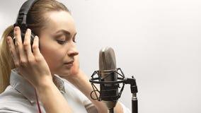 Enregistrement vocal femelle Jeune fille avec le microphone et les écouteurs dans le studio d'enregistrement Enregistrement de vo images stock