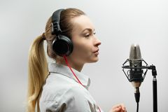 Enregistrement vocal femelle Jeune fille avec le microphone et les écouteurs dans le studio d'enregistrement Enregistrement de vo images libres de droits