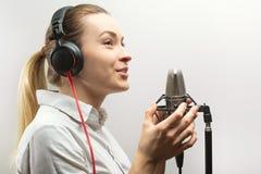 Enregistrement vocal femelle Jeune fille avec le microphone et les écouteurs dans le studio d'enregistrement Enregistrement de vo photo libre de droits