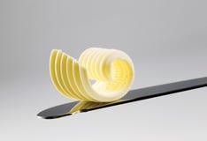 Enrollamiento de la mantequilla en un cuchillo foto de archivo