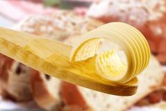 Enrollamiento de la mantequilla en una cuchara de madera imágenes de archivo libres de regalías