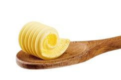 Enrollamiento de la mantequilla en una cuchara de madera Imagen de archivo libre de regalías
