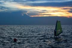 Enrolle la silueta de la persona que practica surf sobre la puesta del sol del mar, actividades del deporte Imagen de archivo