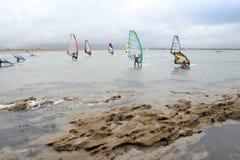Enrolle a las personas que practica surf que hacen frente a la tormenta y las rocas fuertes Foto de archivo libre de regalías