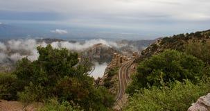 Enroulement sinueux de route de montagne autour des rochers et de la forêt parmi des nuages Images stock