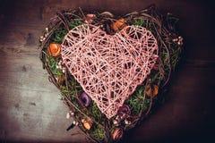 Enrruelle en una forma del corazón hecha de hierba Imagenes de archivo