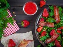 Ensalada útil de la fresa con el arugula, las nueces y el tocino, salsa de la baya Foto de archivo libre de regalías
