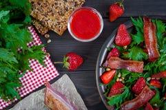 Ensalada útil de la fresa con el arugula, las nueces y el tocino, salsa de la baya Fotos de archivo