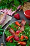 Ensalada útil de la fresa con el arugula, las nueces y el tocino, salsa de la baya Fotografía de archivo