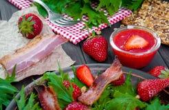 Ensalada útil de la fresa con el arugula, las nueces y el tocino, salsa de la baya Fotos de archivo libres de regalías