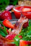 Ensalada útil de la fresa con el arugula, las nueces y el tocino, salsa de la baya Imágenes de archivo libres de regalías